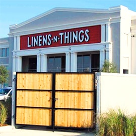 A commercial fence with a steel framed wood security gate surronds Linens -N- Things