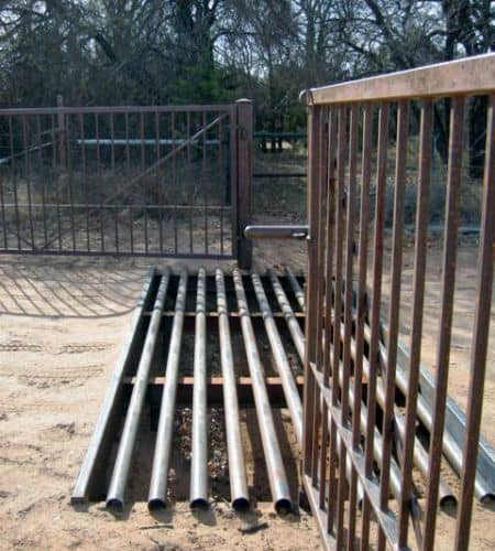 A cattle guard set into the ground at the front gate of a cattle farm