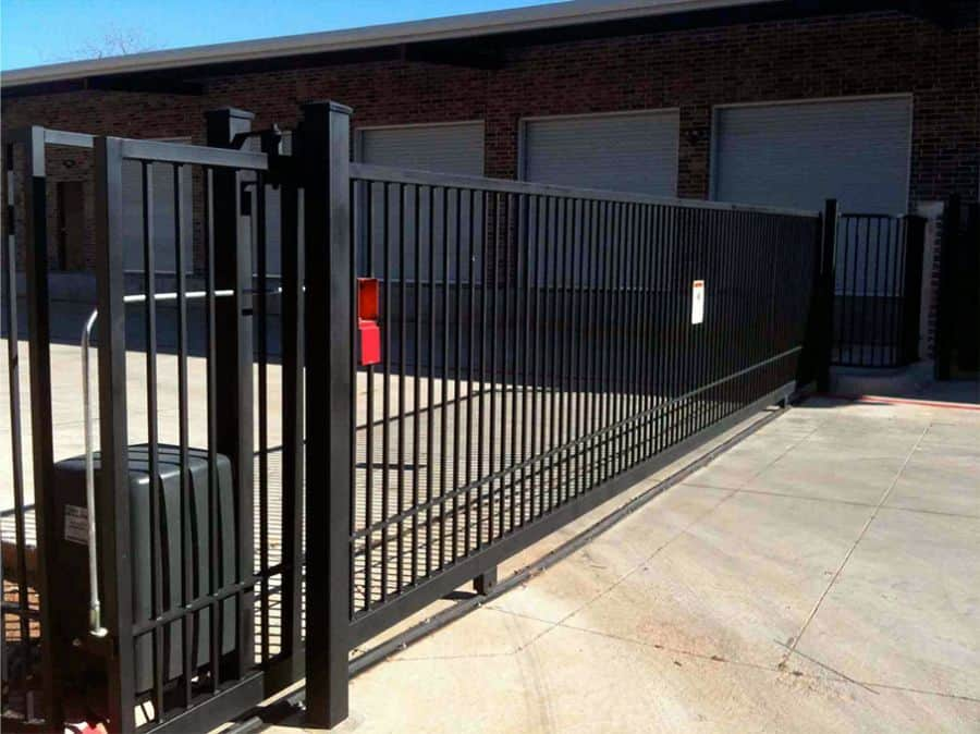 A black steel commercial security gate secures the entrance to a storage facility