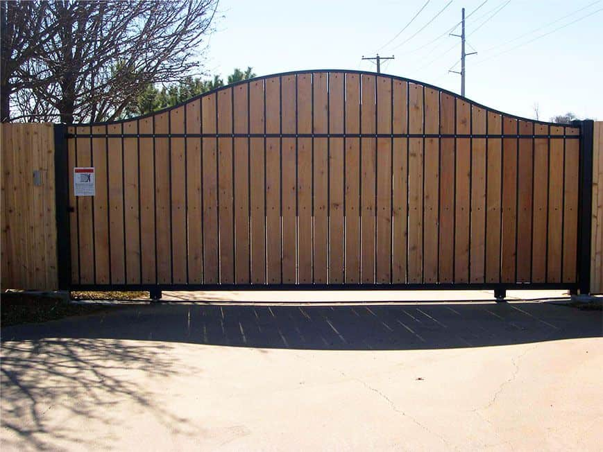 A wood and Iron slide gate secures the entrance to a large property