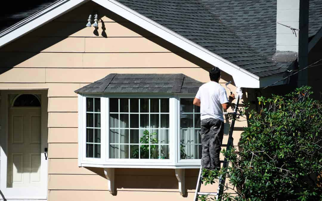 Man painting exterior wooden siding on a house