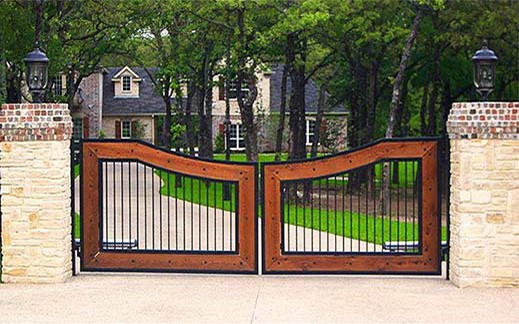 A beautiful wood and steel security gate provides a majestic entrance to a family home