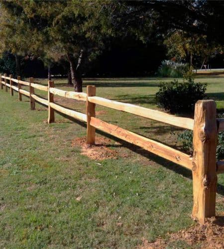 A rural property is lined with cedar split rail fencing