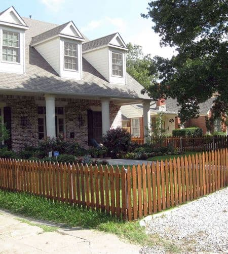 An oak stained wooden picket fence lines the front yard of a family home