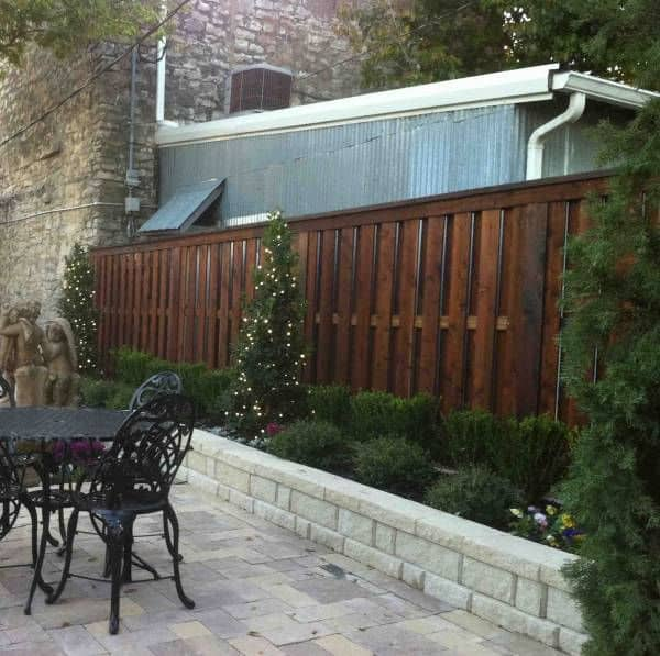 Well maintained landscaping and wooden shadow box fencing beautifies the border of a perfect back yard