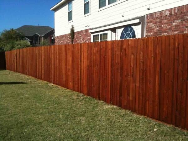 A dark oak stained wooden fence lines a well manicured lawn
