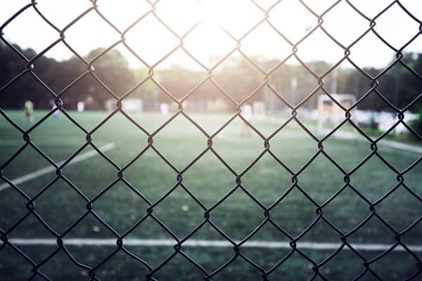 A view of a soccer field through a chain link fence