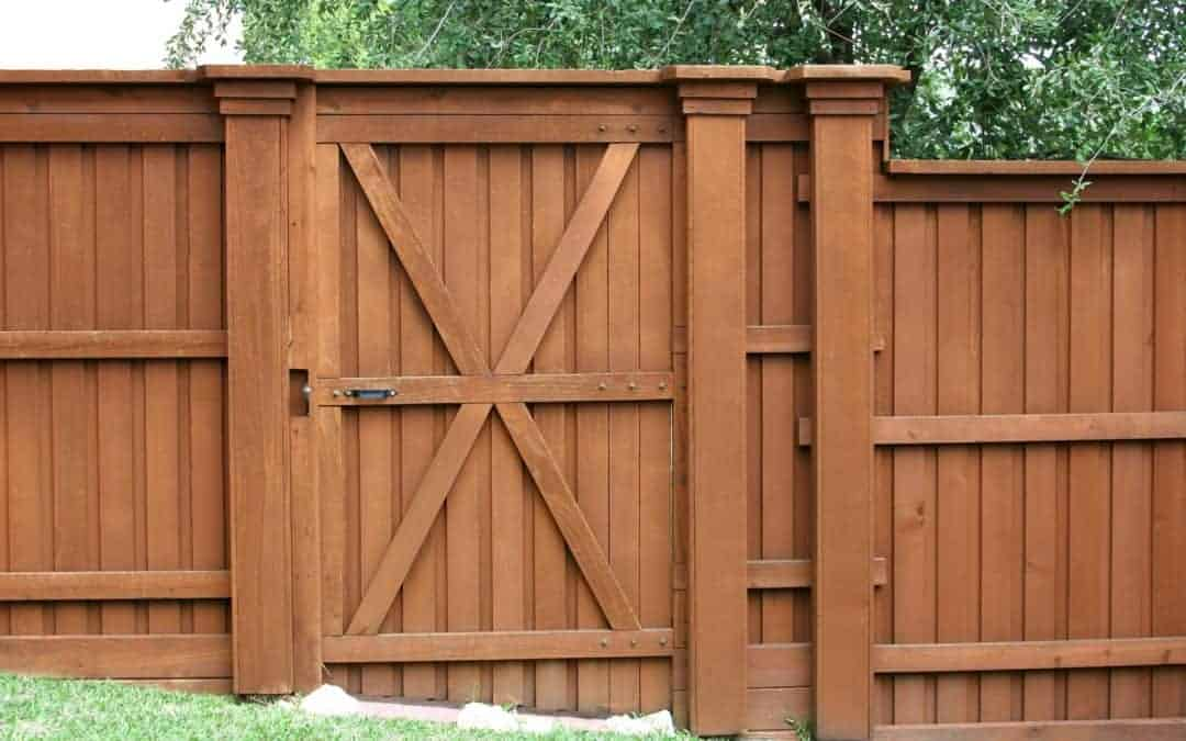 A Tall pressure treated pine privacy fence with a heavy gate stained a reddish shade of maple