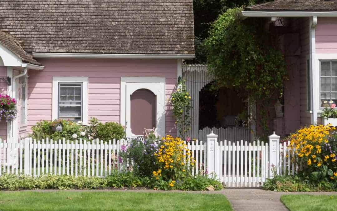 A white stained picket fence accented by flowers and greenery lines the front yard of a pink house