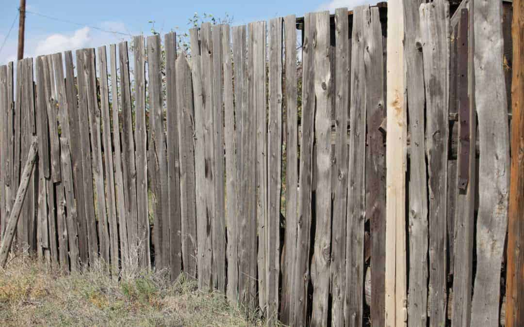 An ugly aging wood fence weathered with age needs to be replaced.