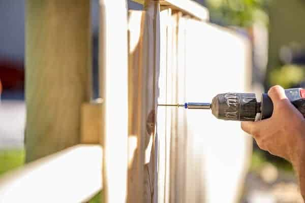Man uses a cordless screwdriver to set a screw into the support of a new fence