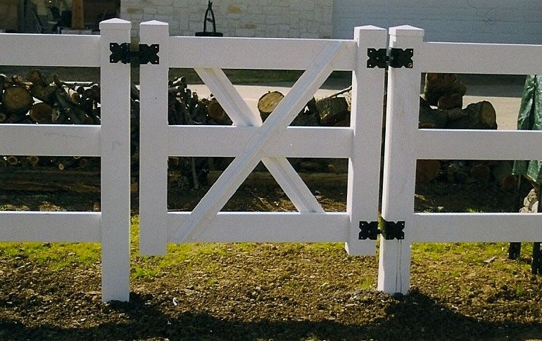 Close up of the gate of a white wooden rail fence with black decorative hardware