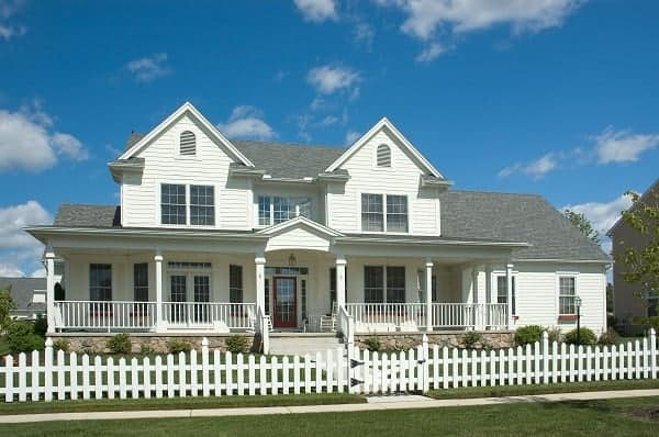 A white picket fence lines the yard of a classic colonial home