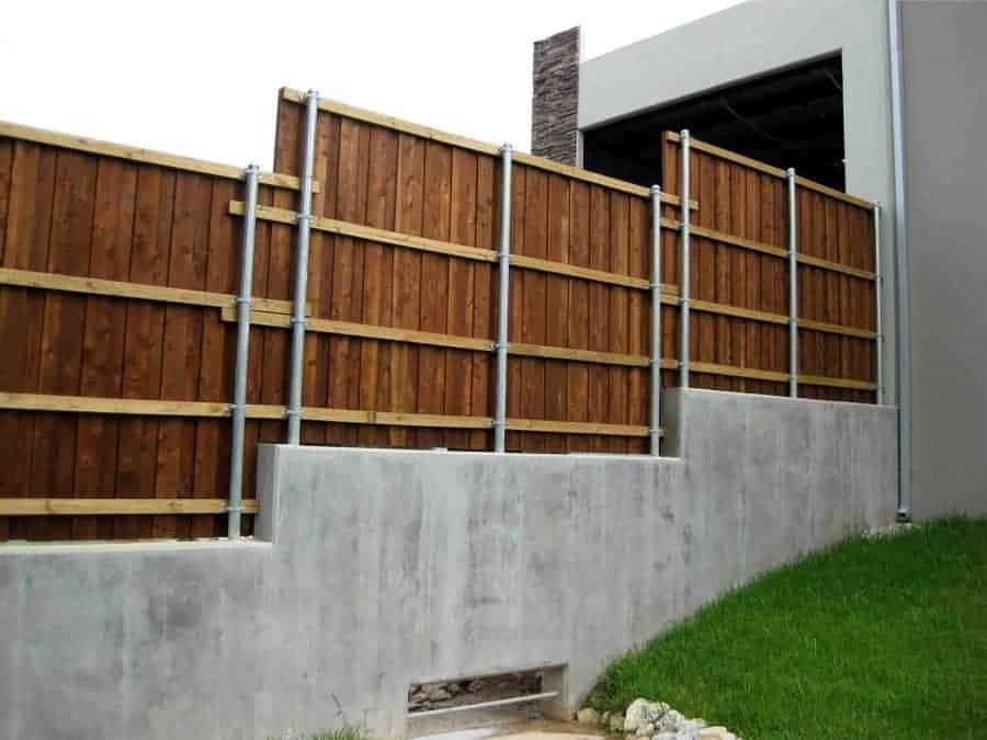 Steel supports set into a concrete wall support a wooden fence