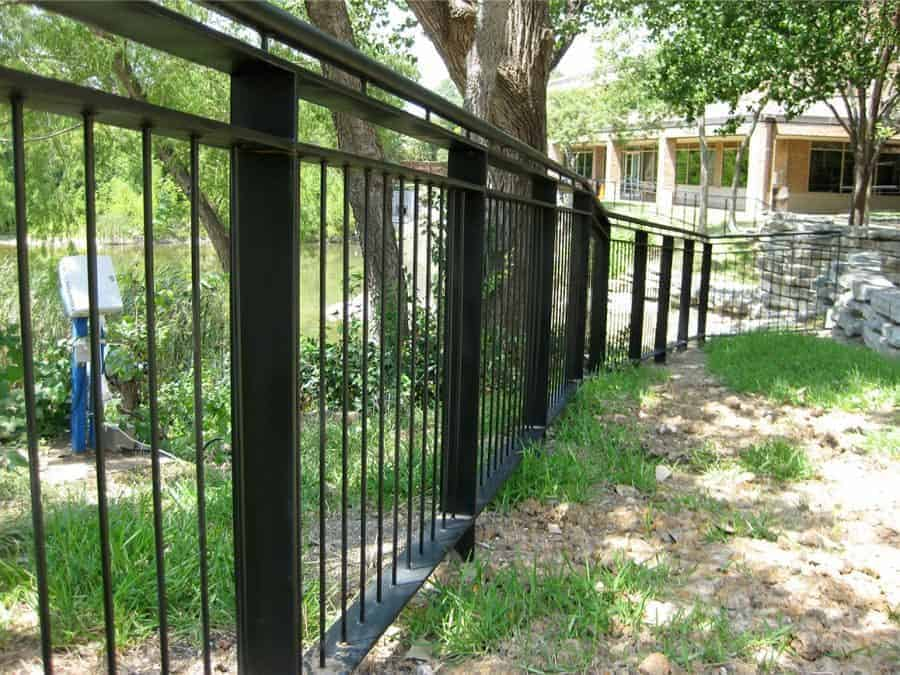 A sturdy steel fence painted black lines a commercial property