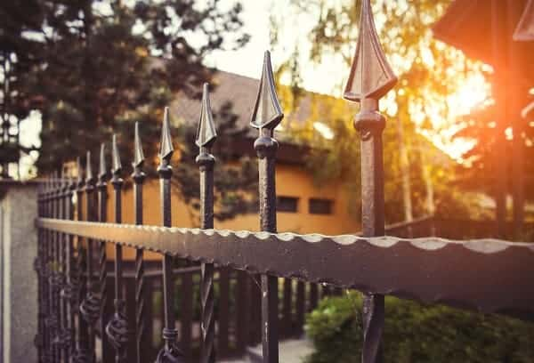 The sun sets through the spear head tips of a decorative wrought iron fence