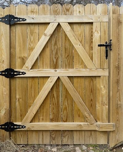 A solid new backyard wood gate with black metal hardware.