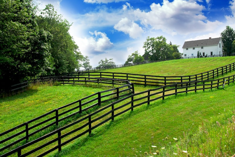 Ebony stained wood rail fences line a rural landscape with lush green fields and farm house in Colleyville, Tx