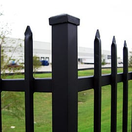 A large logistics center is seen through the bars of a sturdy steel security fence