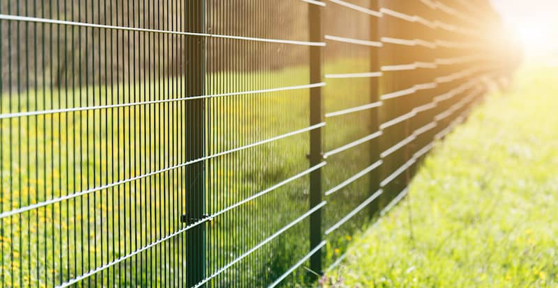 Metal fence leaving in perspective with the sun on grass background on the edge of a Hurst Tx field