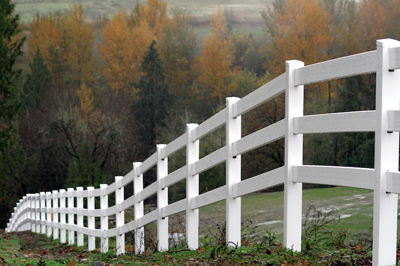 Scenic view of a white fencing heading down a Fort Worth hill during autumn season.