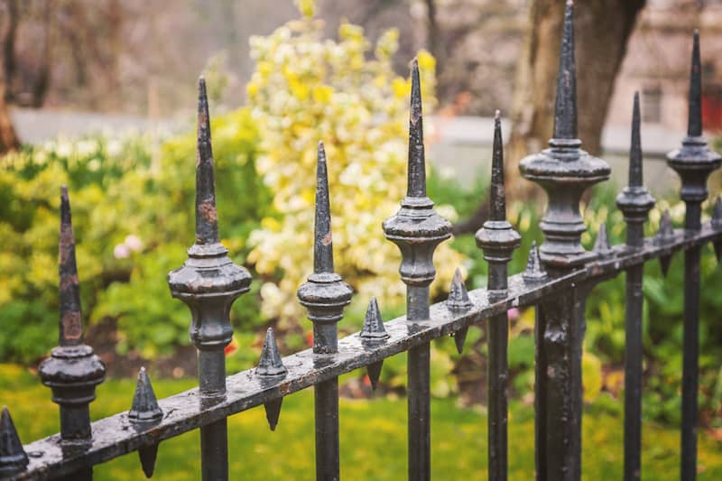 Close up view of a decorative cast iron fence in park.