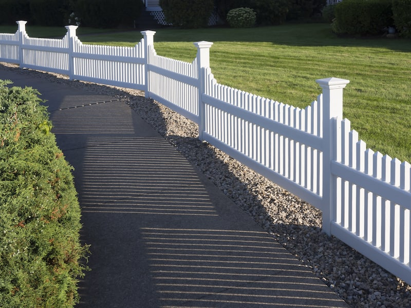 A white wooden picket fence runs along a driveway in Southlake, tx