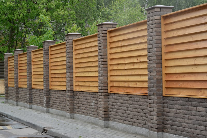 A decorative Brick and Wooden Fence secures a Grapevine Tx property