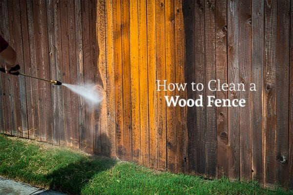 "A person power washing a dirty wood fence with the words ""How to Clean a Wood Fence"""