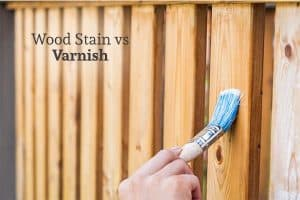 A person using a brush to add stain to a wood fence